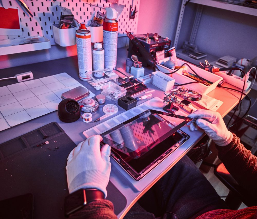 The technician repairs a broken tablet computer in a modern repair shop. Illumination with red and blue lights